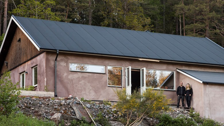 Två personer står framför ett putsat hus med papptak.
