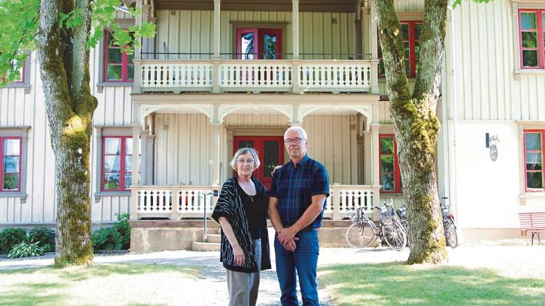 Ett äldre par står framför sitt trähus