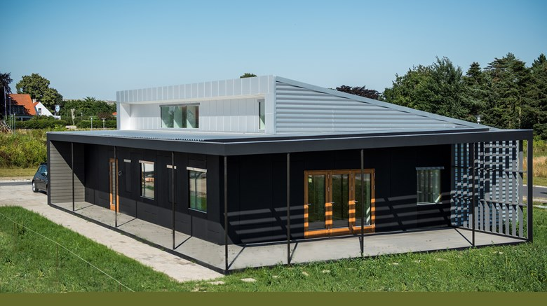 Villa i svart trä och plåt uppfört av återbrukat material